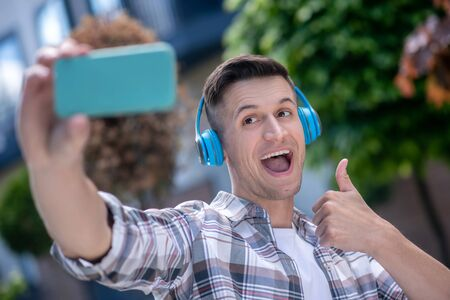 Free time. Cheerful dark-haired male wearing headphones, making selfie, smiling, thumb up Фото со стока
