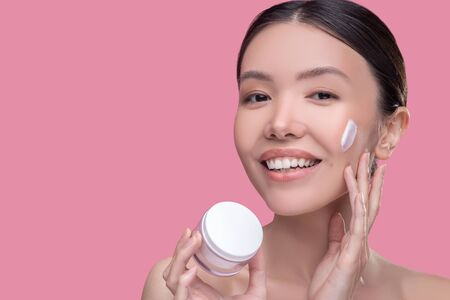 Anti-age cream. Pretty asian girl applying cream on her face and smiling