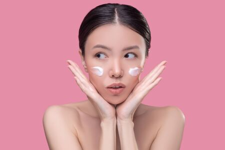 Anti-age. Pretty asian girl applying cream on her face