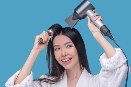 Hair styling. Brunette young asian woman drying her hair and smiling
