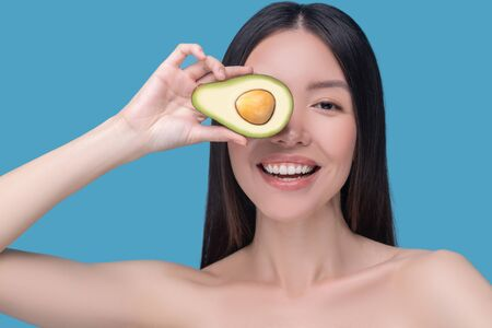 Healthy lifestyle. Smiling young asian woman holding avocado and feeling good Imagens