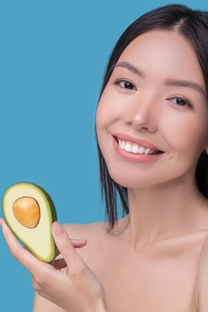 Useful. Smiling young asian woman holding avocado in her hands