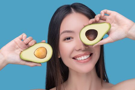 Healthy lifestyle. Smiling young woman holding avocado in her hands Imagens
