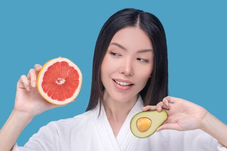 Healthy. Young asian woman holding a half of avocado and slice of grapefruit Imagens
