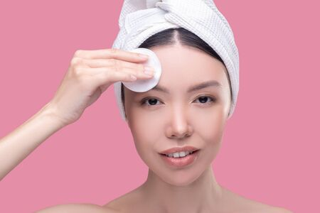 Face cleaning. Pretty asian girl in a white headscarf cleaning her face with a sponge