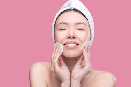 Pleasant procedures. Smiling asian girl in a white headscarf holding sponges for cleaning and feeling pleased Imagens