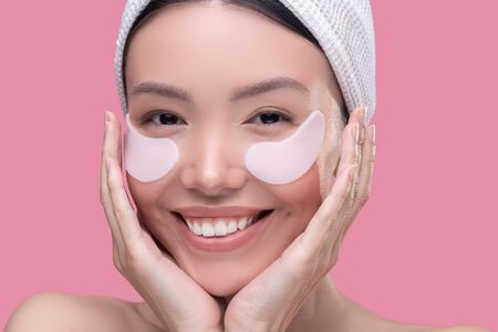 Beauty care. Smiling asian girl in a white headscarf applying patches under her eyes