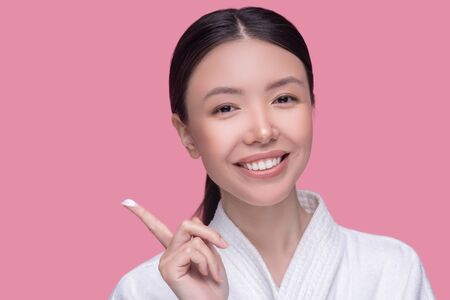 Cream. Pretty asian girl smiling and showing cream on her finger