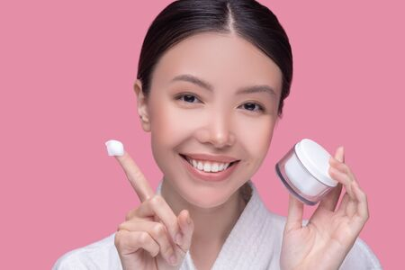 Beauty care. Pretty asian girl taking cream from a jar and looking pleased Imagens