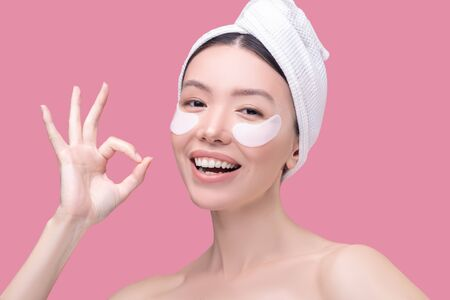 OK. Smiling asian girl in a white headscarf smiling and feeling good Imagens