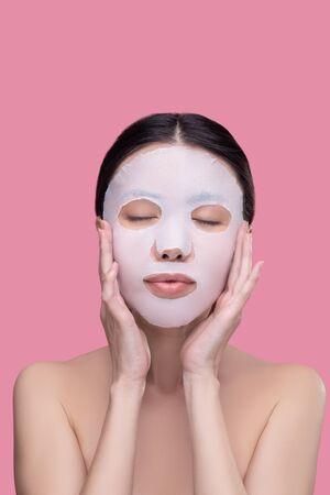 Relaxed. Dark-haired asian girl applying moisturizing mask on her face and feeling relaxed