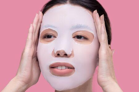 Moisturizing. Dark-haired asian girl applying moisturizing mask on her face