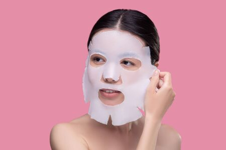 Beauty procedures. Dark-haired asian girl taking off the facial mask Imagens