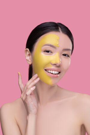 Yellow clay mask. Dark-haired pretty asian girl having face beauty procedures