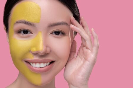 Face care. Dark-haired pretty asian girl having facial mask and looking enjoyed Imagens