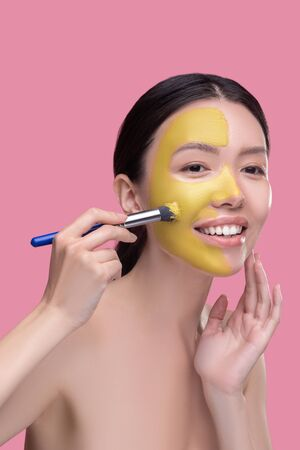 Clay mask. Dark-haired pretty asian girl applying clay facial mask and looking contented