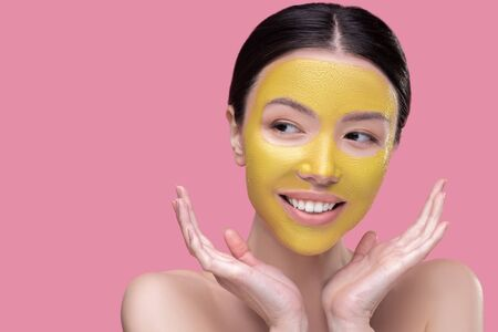 Facial mask. Dark-haired pretty asian girl having facial mask and looking contented