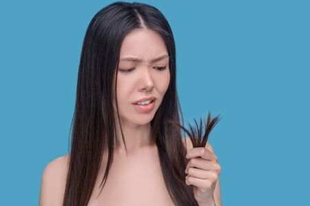 Hair care. Young asian woman looking at her hair ends and feeling unsatisfied Imagens