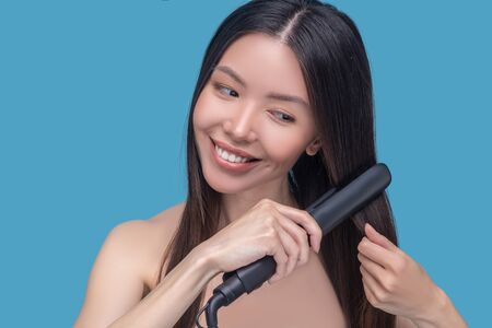 Hair styling. Young asian woman straightening hair and feeling pleased Imagens