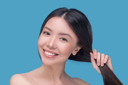 Good hair. Beautiful woman holding her healthy hair and smiling nicely