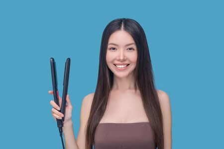Hair styling. Young asian woman holding hair straightening iron and smiling nicely