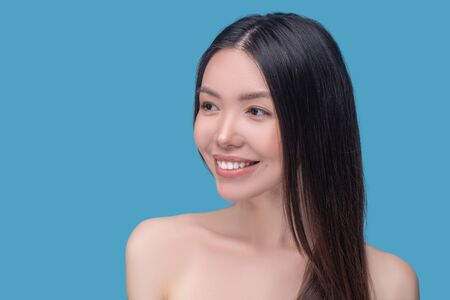Wellness. Beautiful woman with long and healthy hair smiling nicely
