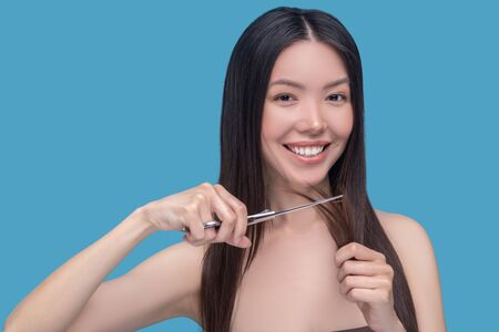 New hair style. Young asian woman cutting her hair and looking excited