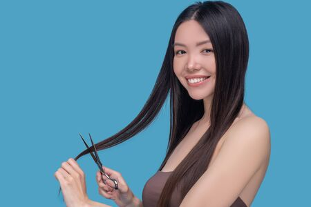 Haircut. Young asian long-haired woman holding scissors and smiling
