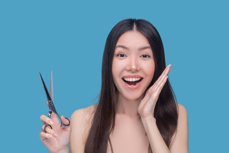 Hair cutting. Young asian woman holding scissors and looking excited