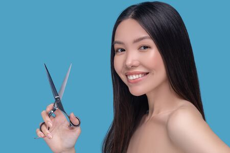 Haircut. Young asian woman holding scissors and smiling