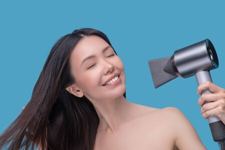 Hair care. Brunette young asian woman drying her hair and enjoying Imagens
