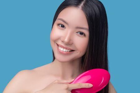 Hair treatment. Brunette young asian woman brushing her hair and feeling good