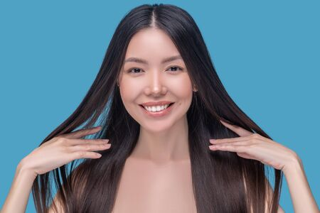 Healthy hair. Beautiful woman holding her healthy hair and feeling amazing