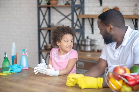 Get ready for housework. African american bearded man in yellow gloves talking to his cute kid Banco de Imagens