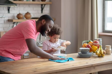 Dream team. Tall dark-skinned man in a pink tshirt wiping the table and smiling, his daughter wiping the plate