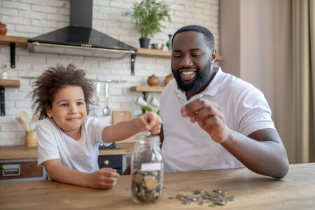 Saving money. Dark-skinned bearded man holding a coin into his hand