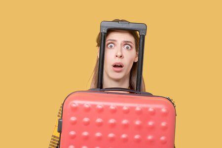 Surprise, fear. Frightened young adult girl with open mouth and big eyes peeking out from behind a red suitcase.