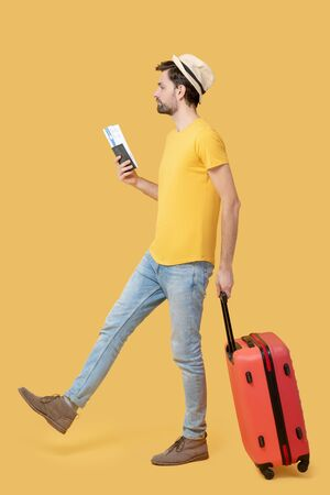 Traveler. Young adult man in a tshirt and jeans hat walking with a ticket in his hand and a suitcase on wheels