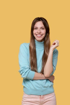 Good mood. Young adult girl standing in a light-blue sweater with rolled up sleeves, smiling in a good mood.
