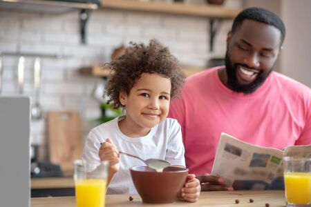 Breakfast together. Dark-haired african american father having a nice morning with his kid