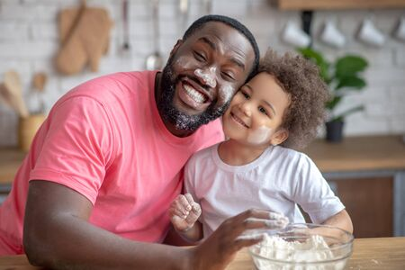 Happy people. Dark-skinned father looking funny with face stained with flour, his daughter smiling