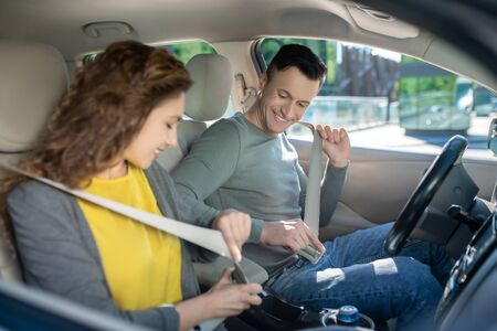 In the car. Young couple sitting in the car, woman fixing her safety belt 免版税图像