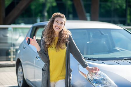 Smiling curly pretty woman with keys standing near a gray car, resting her hand on him