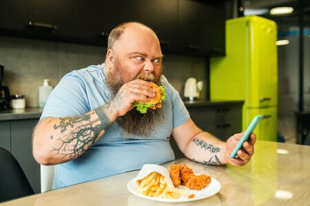 Video call, snack. Bearded fat man with tattoos looking at smartphone bite burger with eyes wide open Standard-Bild