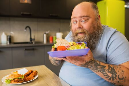Shock, emotions. Fat very surprised man with open mouth and grimace looking at chopped fresh vegetables in lunchbox, bringing it to his face