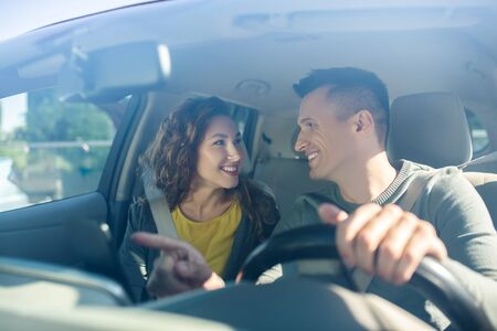 Young man driving a hand near the GPS navigator, looking at the woman nearby, smiling sitting in the car Banque d'images