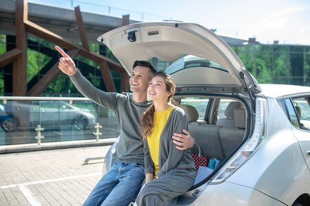 Smiling man hugging woman near car trunk pointing hand up, happy