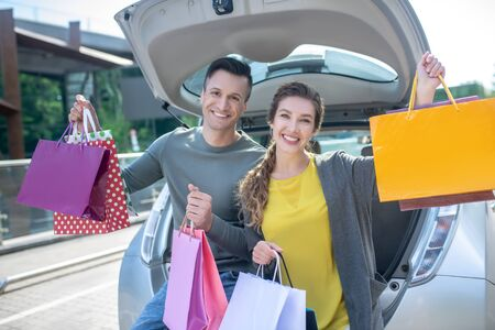 Young cheerful woman and man holding many multi-colored bags with purchases in their raised hands, standing enthusiastic near car Foto de archivo