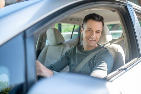 Young adult smiling man driving a car, looking out the open window at the mirror