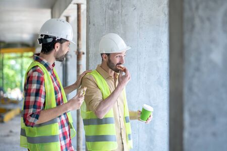 Building site. Building workers in yellow vests and helmets having coffee with sandwiches, discussing something